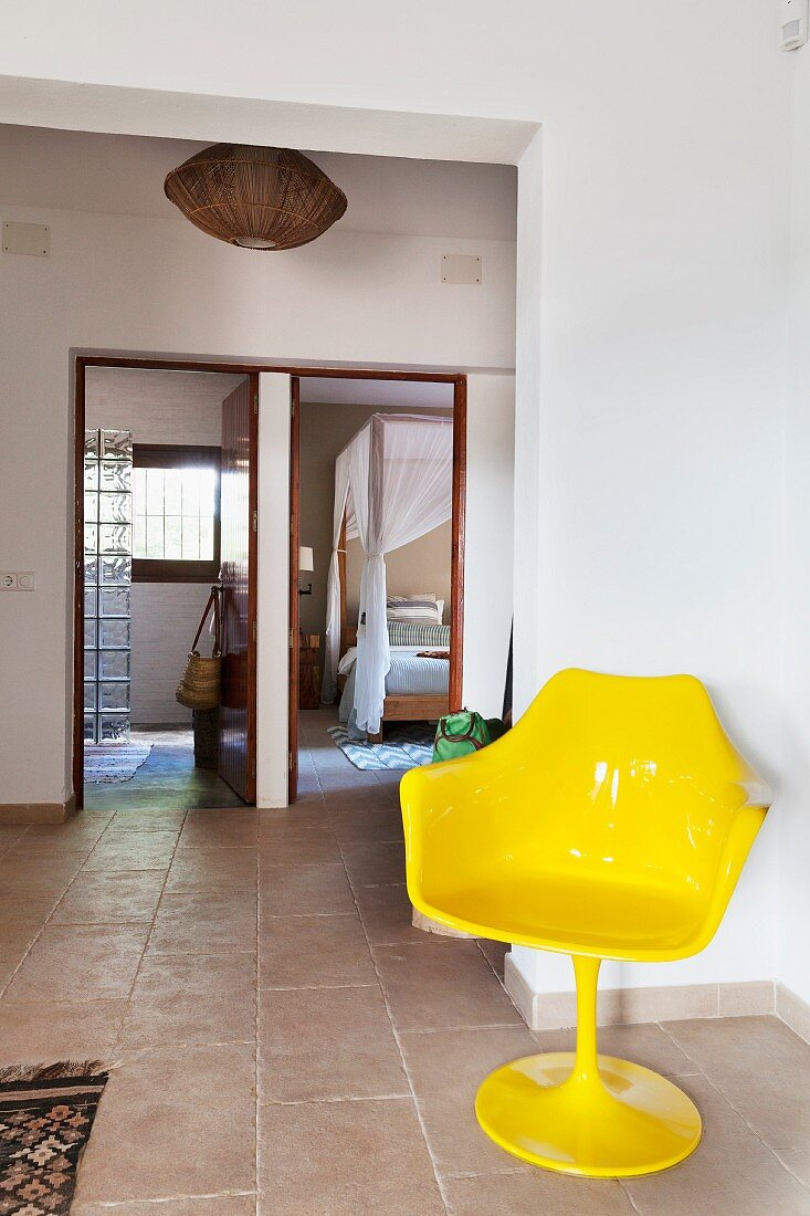 Yellow tulips chair in foyer with stone-flagged floor; view through open doors into bathroom and bedroom in background