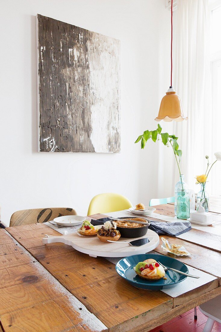 Rustic dining table in front of modern artwork on wall