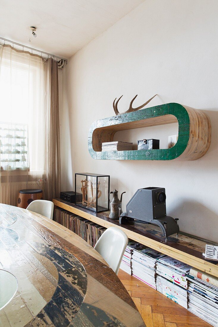 View across dining set of hand-crafted, curved shelf above sideboard with collection of magazines