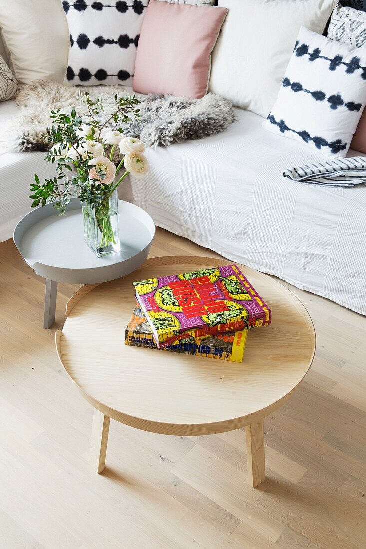 Set of tables, one grey and one in natural wood, in front of corner couch with loose cover