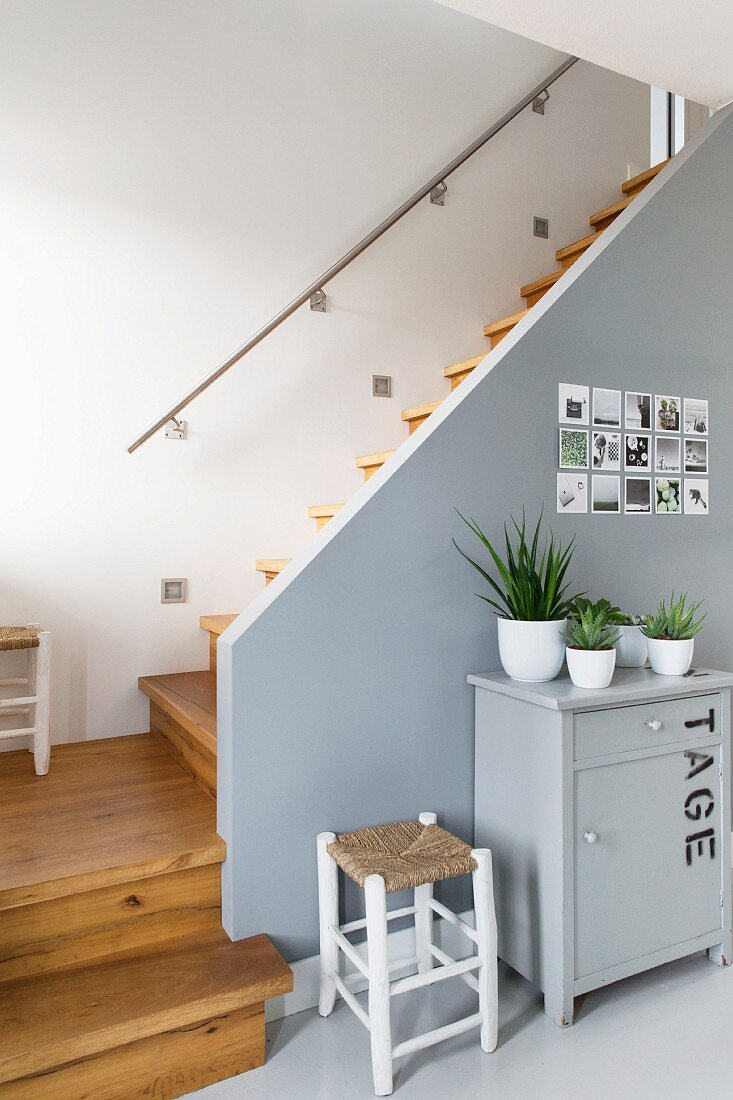 Potted plants on cabinet and stool against grey-painted side wall of wooden staircase