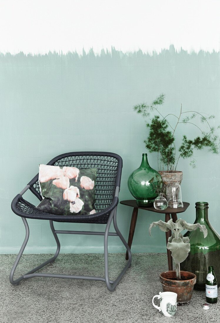 Hand-crafted cushion cover with photo print on tubular metal chair with woven seat next to collection of vintage bottles