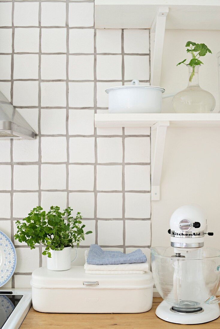 Bread bin and mixer on wooden worksurface below bracket shelves and against white-tiled splashback