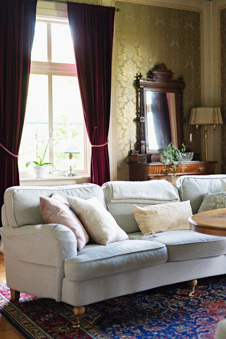 Pale couch with scatter cushions in front of red, gathered curtains on windows in traditional living room