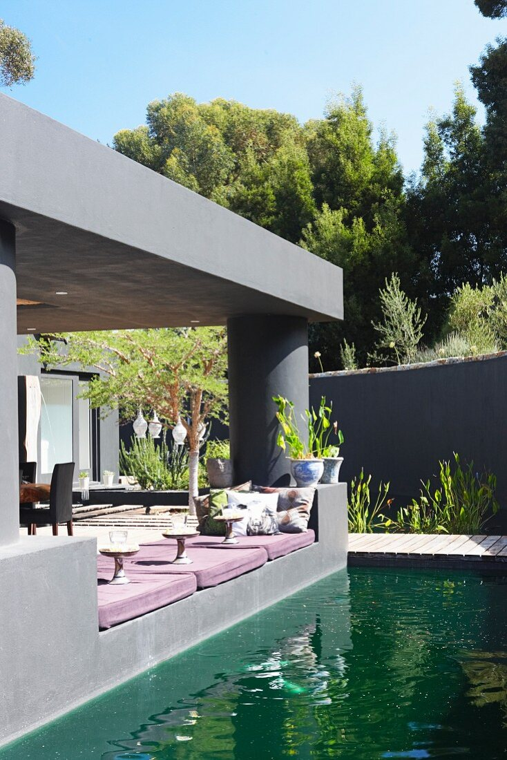 Pond outside modern house with roofed terrace painted grey and comfortable floor cushions on edge