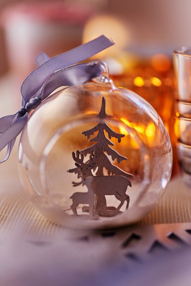 Durchsichtige Christbaumkugel mit Rehfiguren und Tannenbaum als Tischdeko für Weihnachten (Close Up)