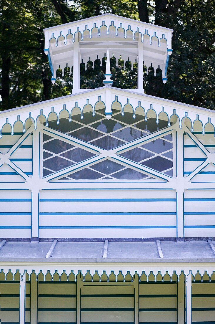 Blue and white striped summer house with diamond lattice window and Oriental-style roof ornament