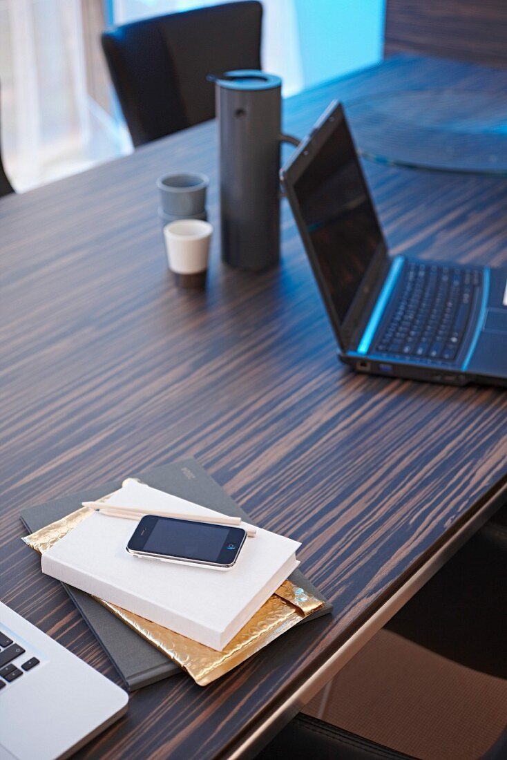 Laptop, thermos flask, book and smartphone on elegant, exotic-wood desk