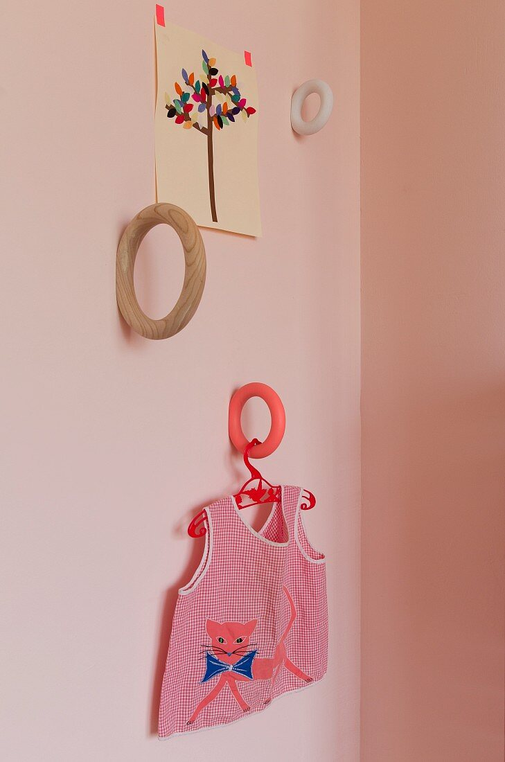 Ring brackets in different colours mounted on wall and child's tunic on coat hanger