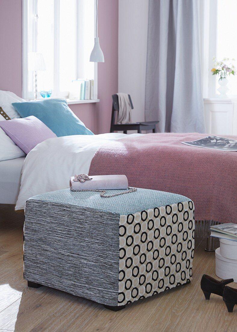 Pouf in Patchwoork-Look als Anlage oder Sitzplatz neben dem Bett mit pastell lila Tagesdecke