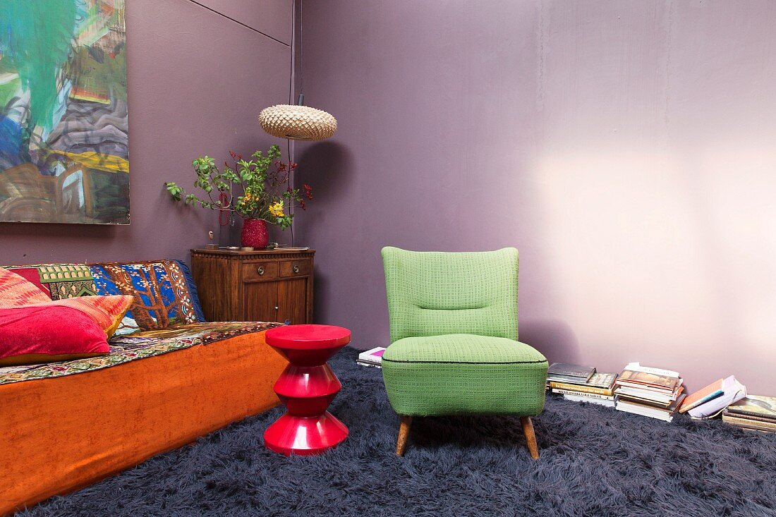 Long-pile carpet and flea-market furnishings in living room with purple walls