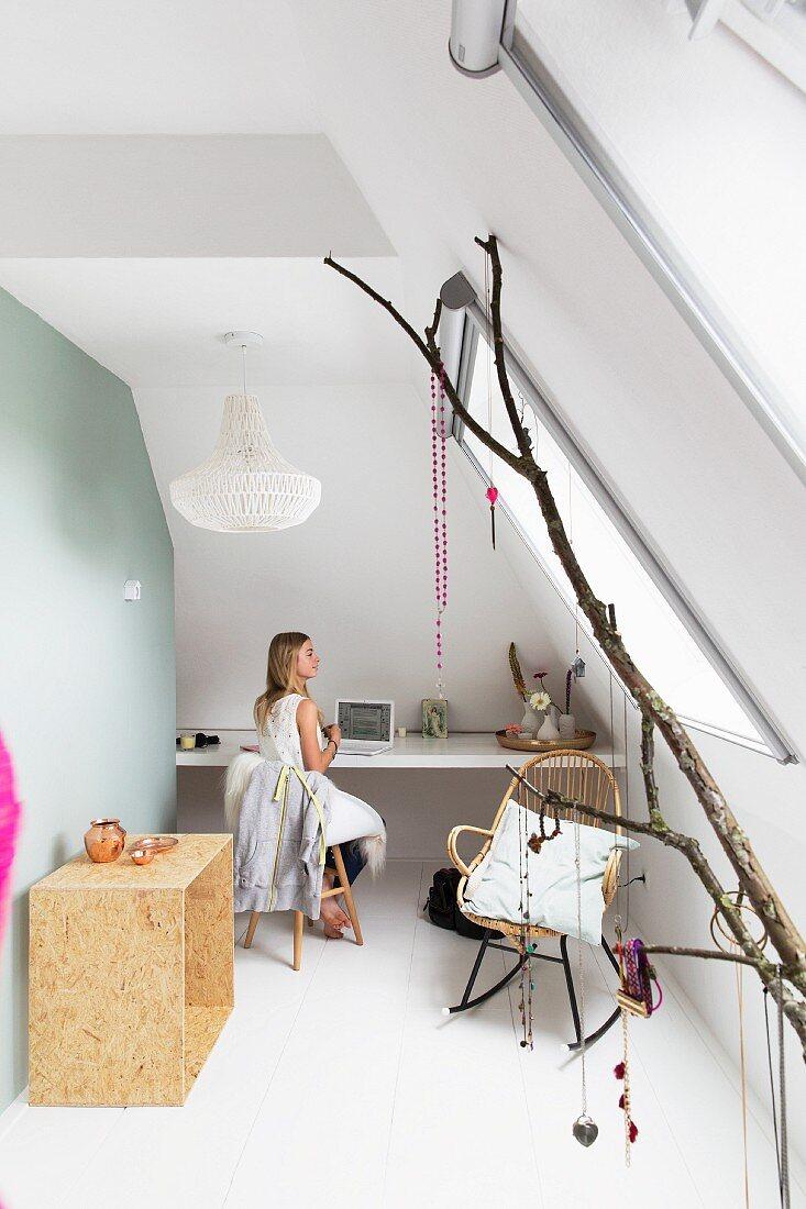 Zimmer mit Dachschräge, eingebautem Schreibtisch und Ast mit aufgehängtem Schmuck