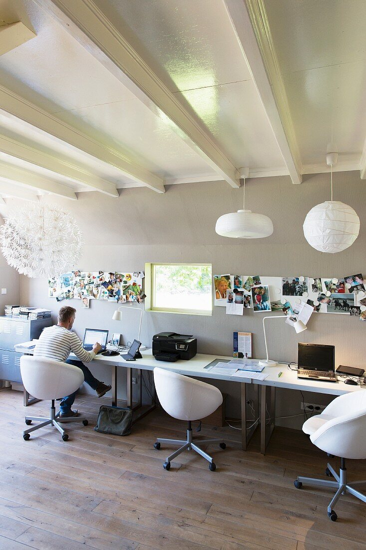 Man sitting at desk with white swivel chairs in modern office with white, wood-beamed ceiling