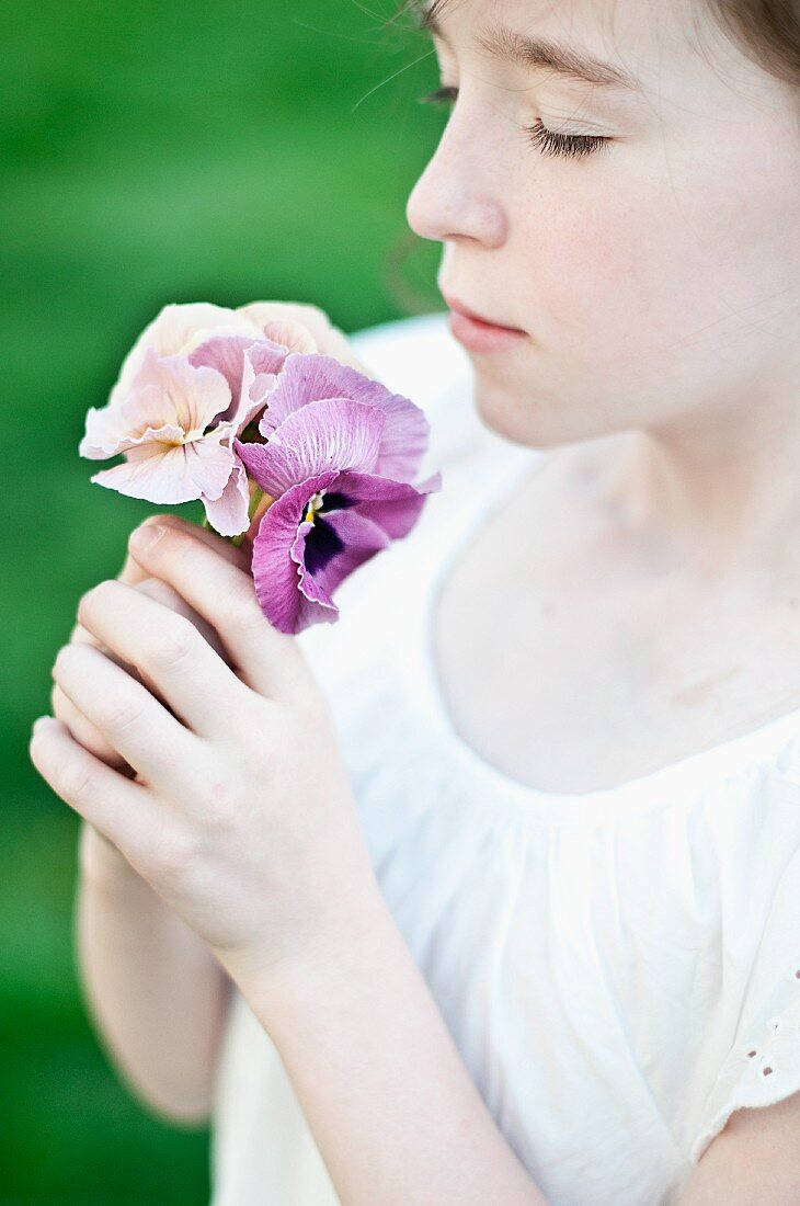 Girl smelling delicate pansies