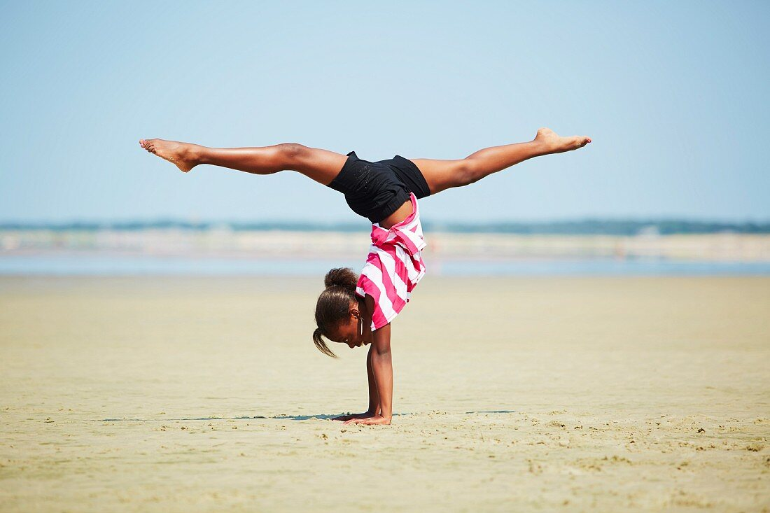 Sporty girl performing handstand on beach