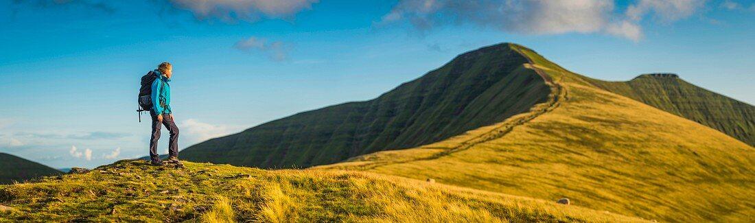 Junger Wanderer auf grasbewachsenem Hügel