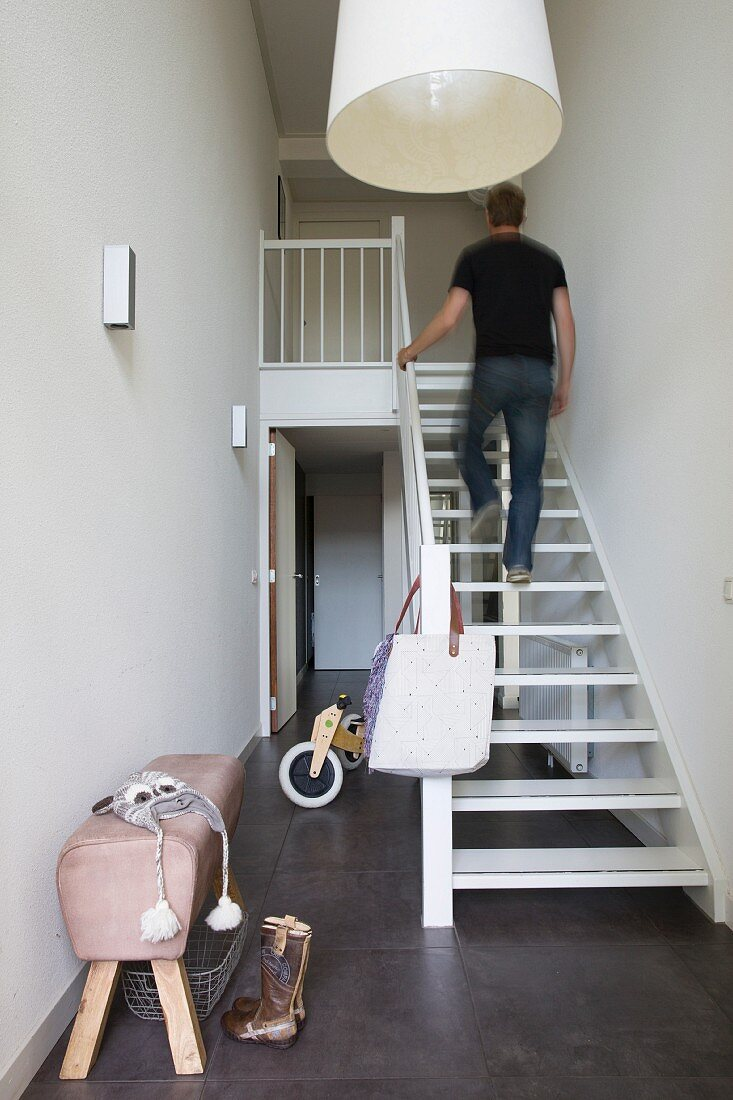 Man walking up white-painted wooden staircase in narrow stairwell with dark grey, tiled floor