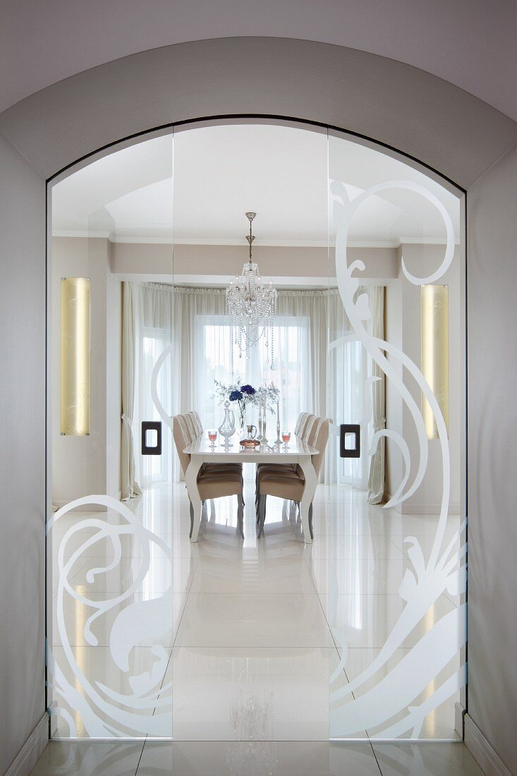View of elegant dining area through arched doorway with open frosted glass sliding doors