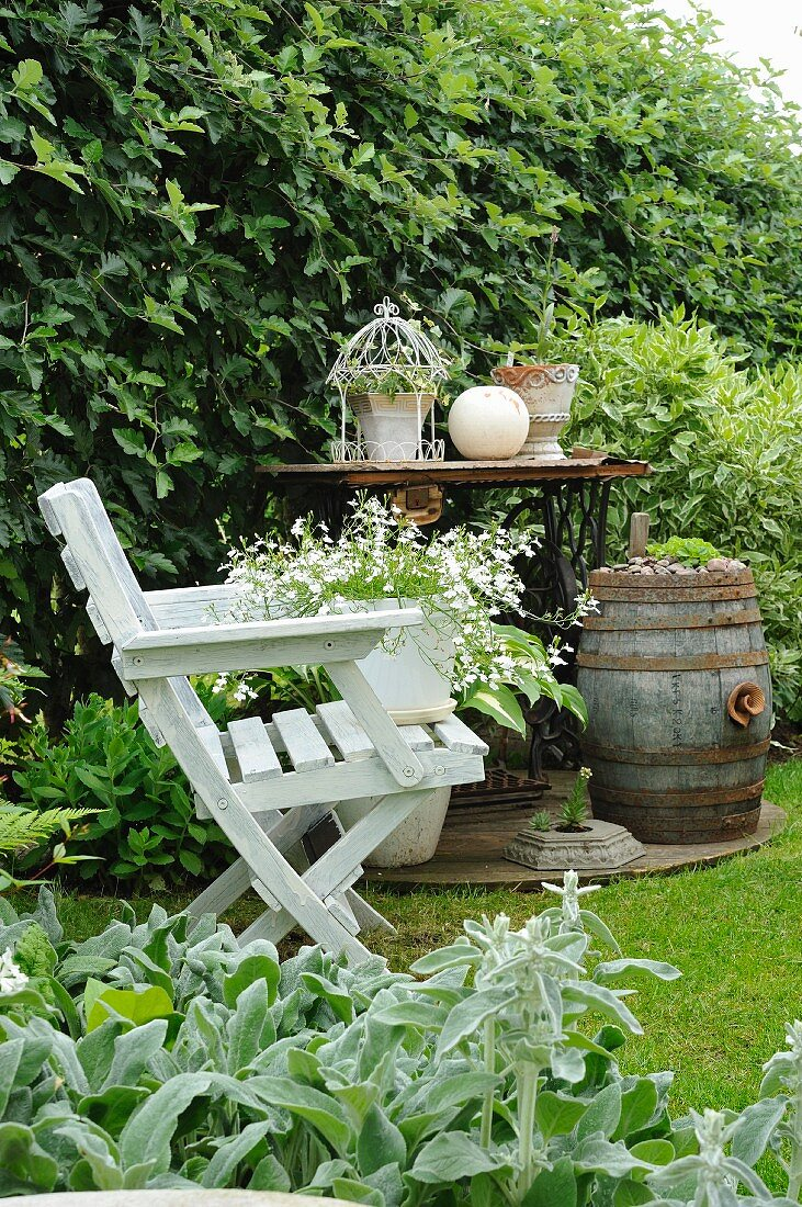 Potted plant on white wooden chair in front of vintage sewing machine used as table and barrel