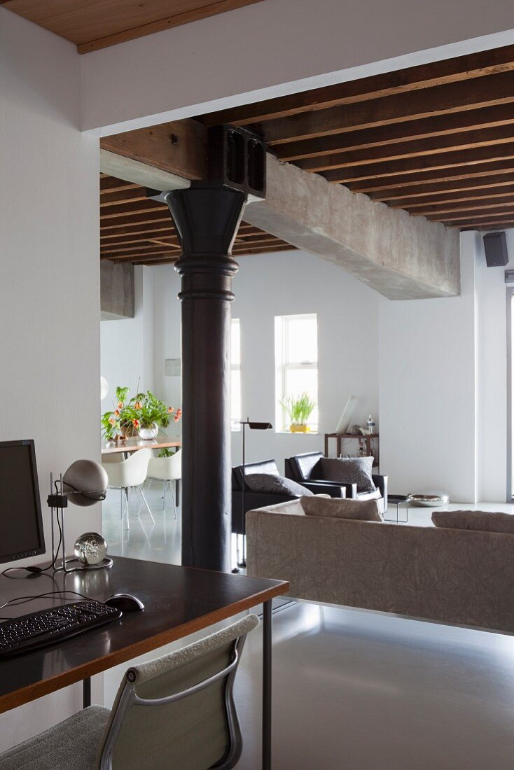 Home office in foreground; open-plan living area in renovated loft apartment with wood-beamed ceiling and concrete girders