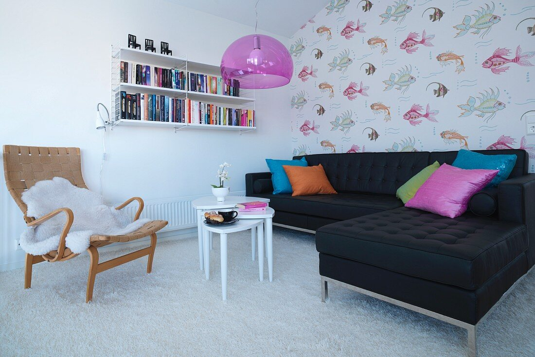 Armchair with animal-skin blanket, black sofa combination, set of white side tables, pale carpet and accent wall with fish-patterned wallpaper