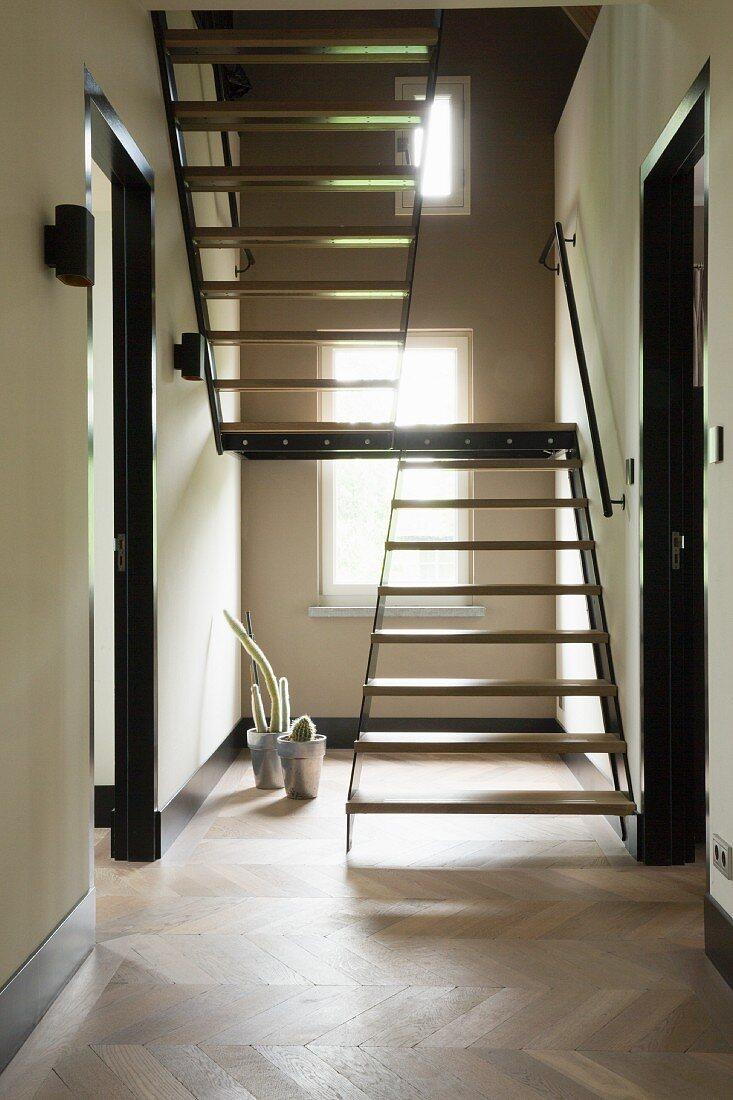 Custom, wood and metal staircase in narrow hallway with herringbone parquet floor