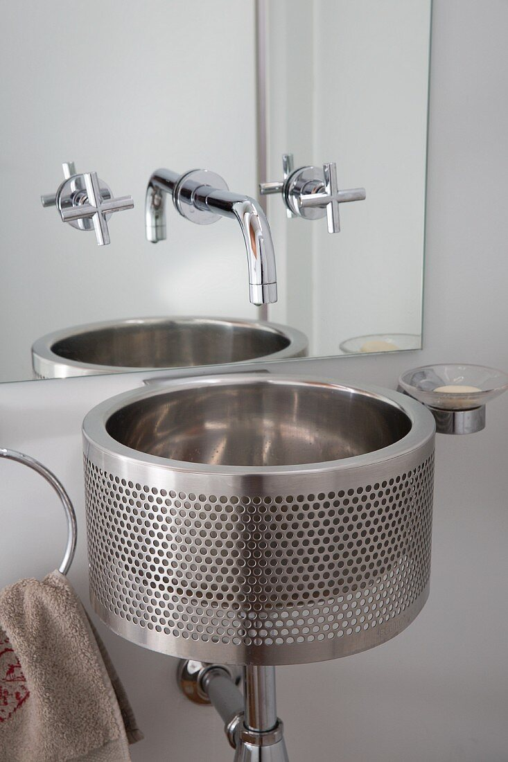 Minimalist, stainless steel washstand below wall-mounted tap fitted on mirror