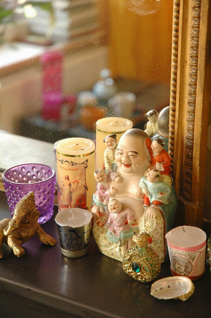 Votive candles around Buddha figurine in front of gilt-framed mirror on surface