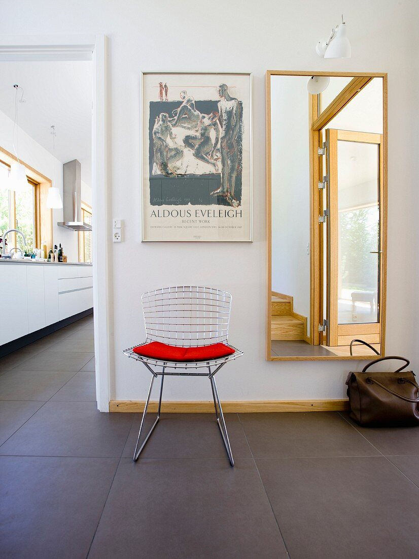 A classic, mesh metal chair and a red cushion in front of a full-length mirror and door at the side open to the kitchen with continuous dark grey tiled floor
