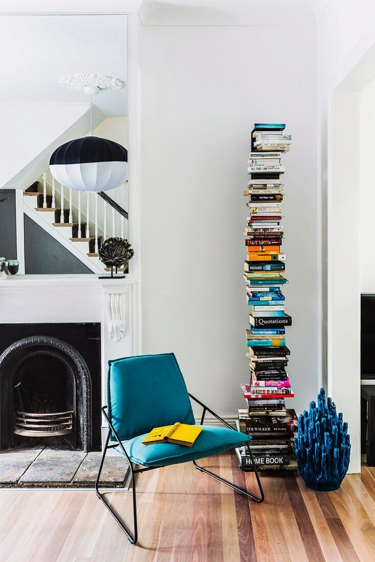 Modern reading area with designer bookcase in front of open fireplace and wooden staircase reflected in mirror