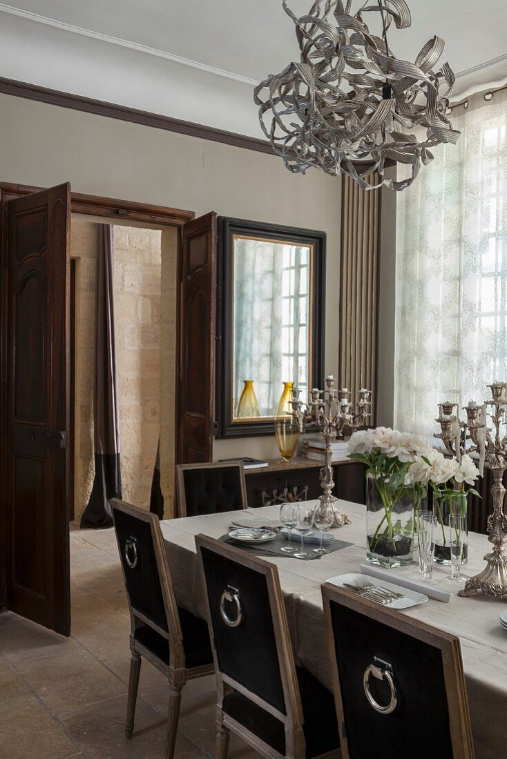 Esstafel mit mehrarmigen Silber Kerzenhaltern und antike Stühle in elegantem Esszimmer