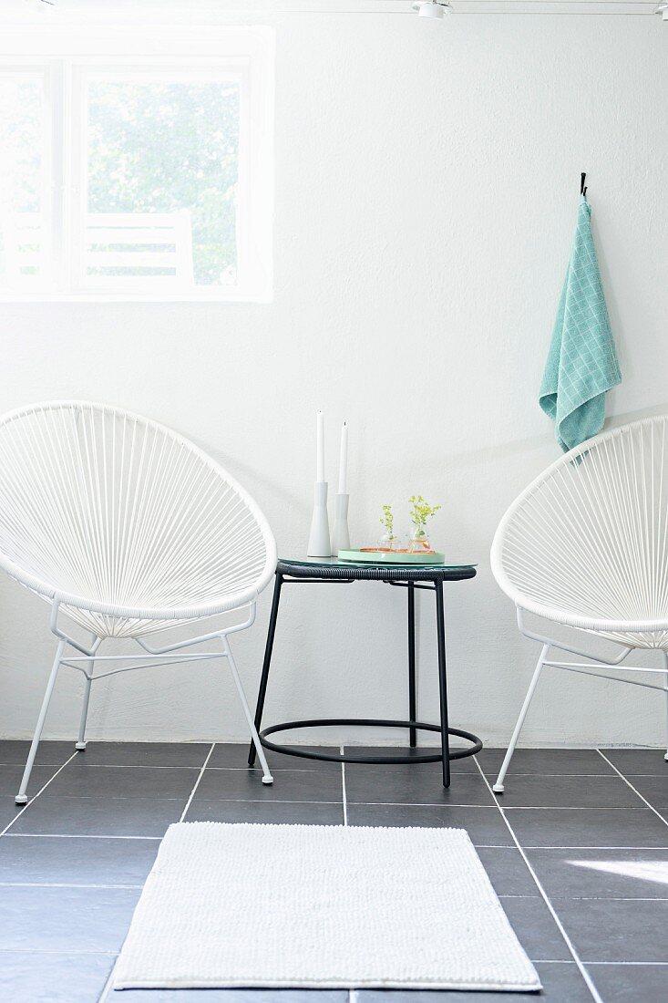 Sessel mit weisser Seilverspannung neben schwarzem, filigranem Beistelltisch, weiße Badematte auf grauem Fliesenboden