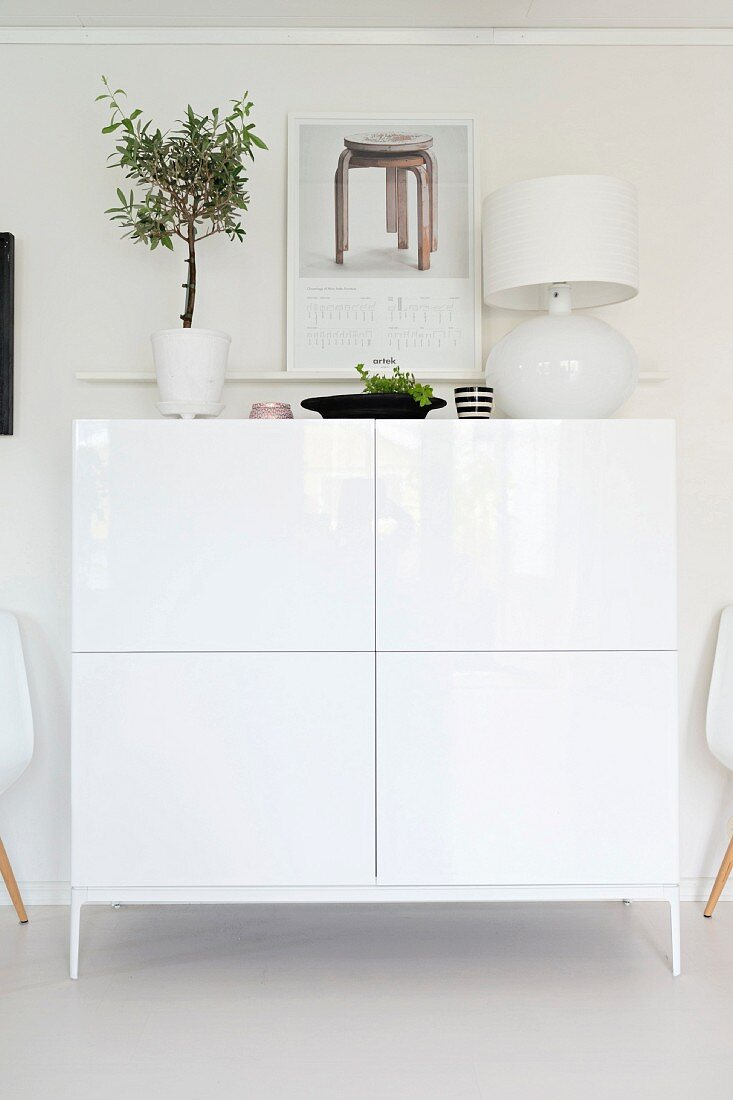 Small, potted tree and white table lamp on top of delicate cabinet on legs with white, glossy front