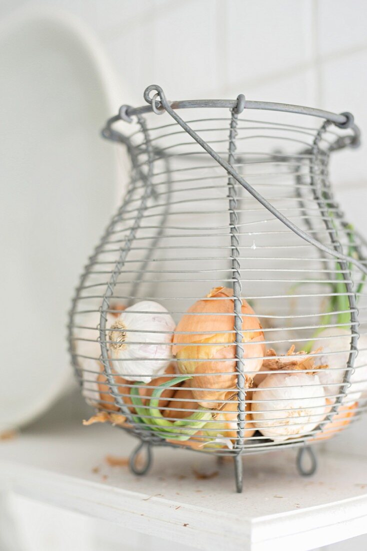 Wire basket of onions and garlic bulbs