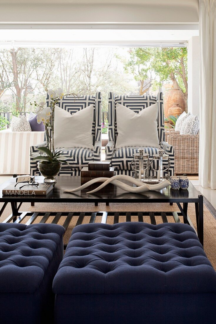 Seating area with blue ottomans and armchairs with geometric-patterned covers