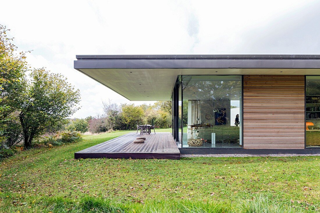 Modern house with roof projecting over terrace in morning light