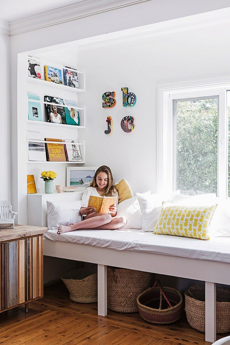Girl sitting reading on built-in day bed below window with baskets stored below