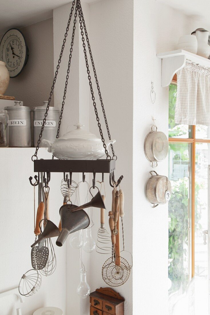 Kitchen utensils hung from metal hoop with hooks suspended from ceiling in rustic kitchen