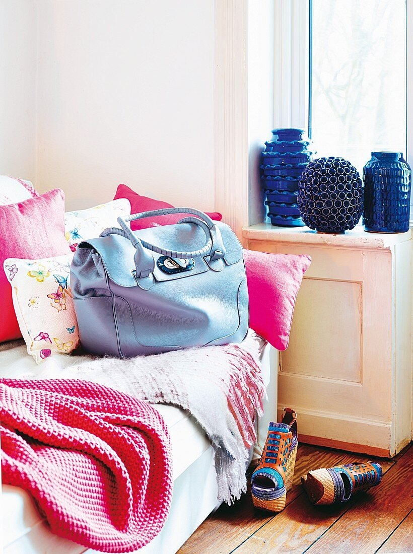 Blue Georgia business bag by Sonja Schweizer on sofa with pink blanket and scatter cushions