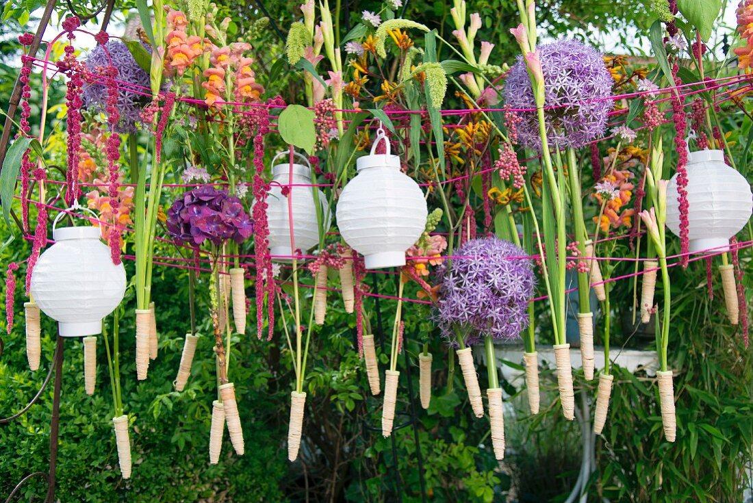 Wäscheleine mit weissen Lampions und Blumen im Garten