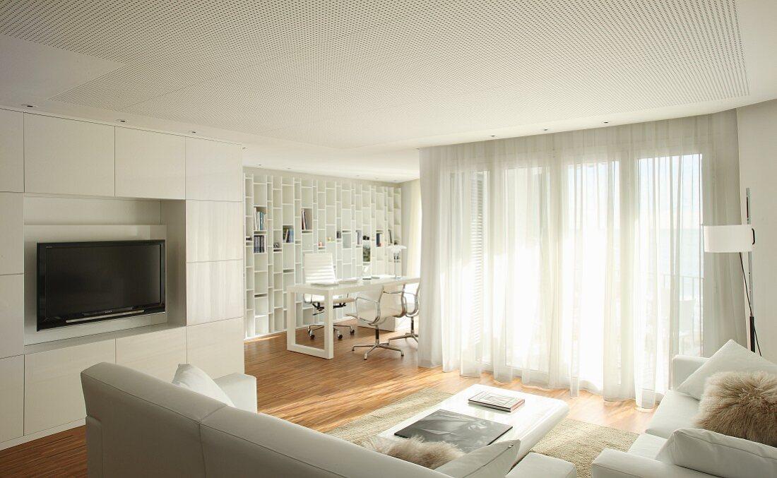 Blick von Sitzgruppe auf integrierte Schrankwand mit Flatscreen; Arbeitsnische mit Aluminium Chairs und Einbauregal im Hintergrund