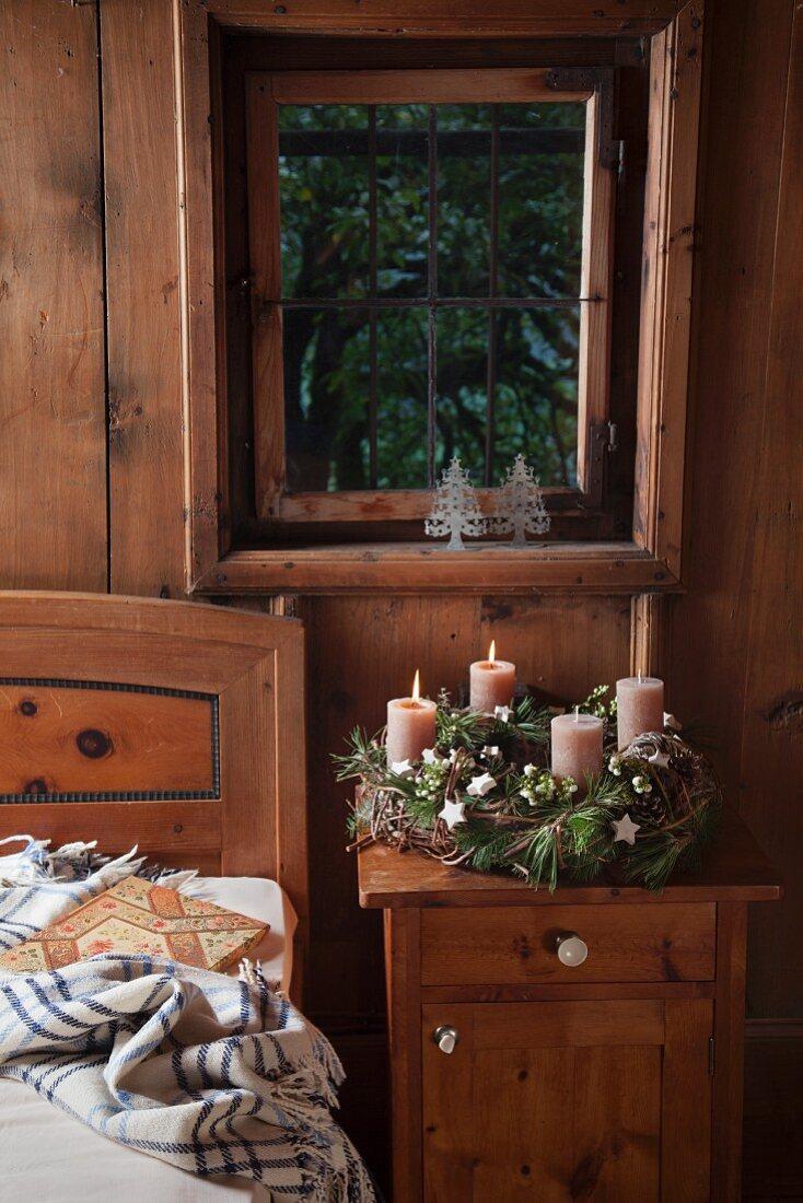 Rustikaler Adventskranz mit zwei brennenden Kerzen in einem bäuerlichen Schlafzimmer