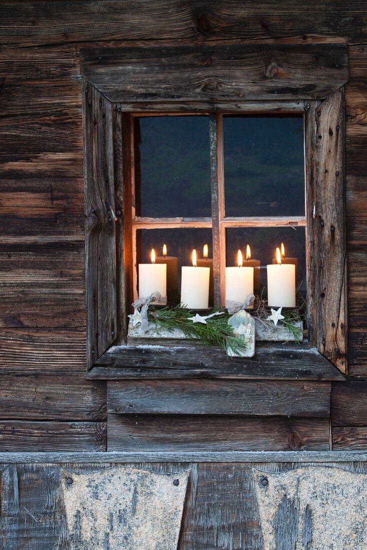 Rustikaler Adventskranz mit vier brennenden Kerzen im Fenster eines verwitterten Holzhauses