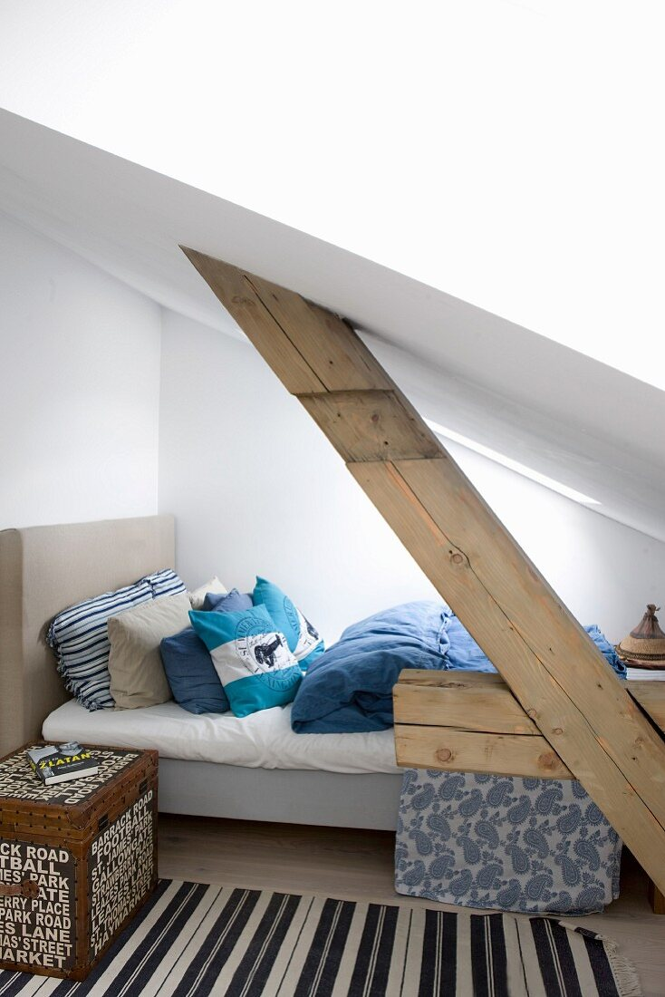 Scatter cushions on bed and wooden cube table under sloping ceiling