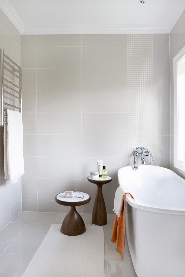 Two-part set of wooden side tables next to free-standing, white bathtub next to window in modern bathroom with vintage atmosphere