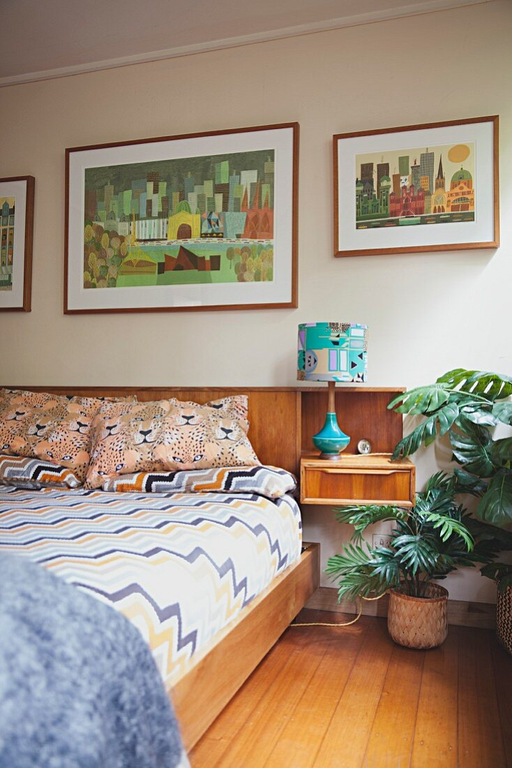 Double bed with wooden frame and bedside table integrated in retro-style headboard below collection of pictures on wall