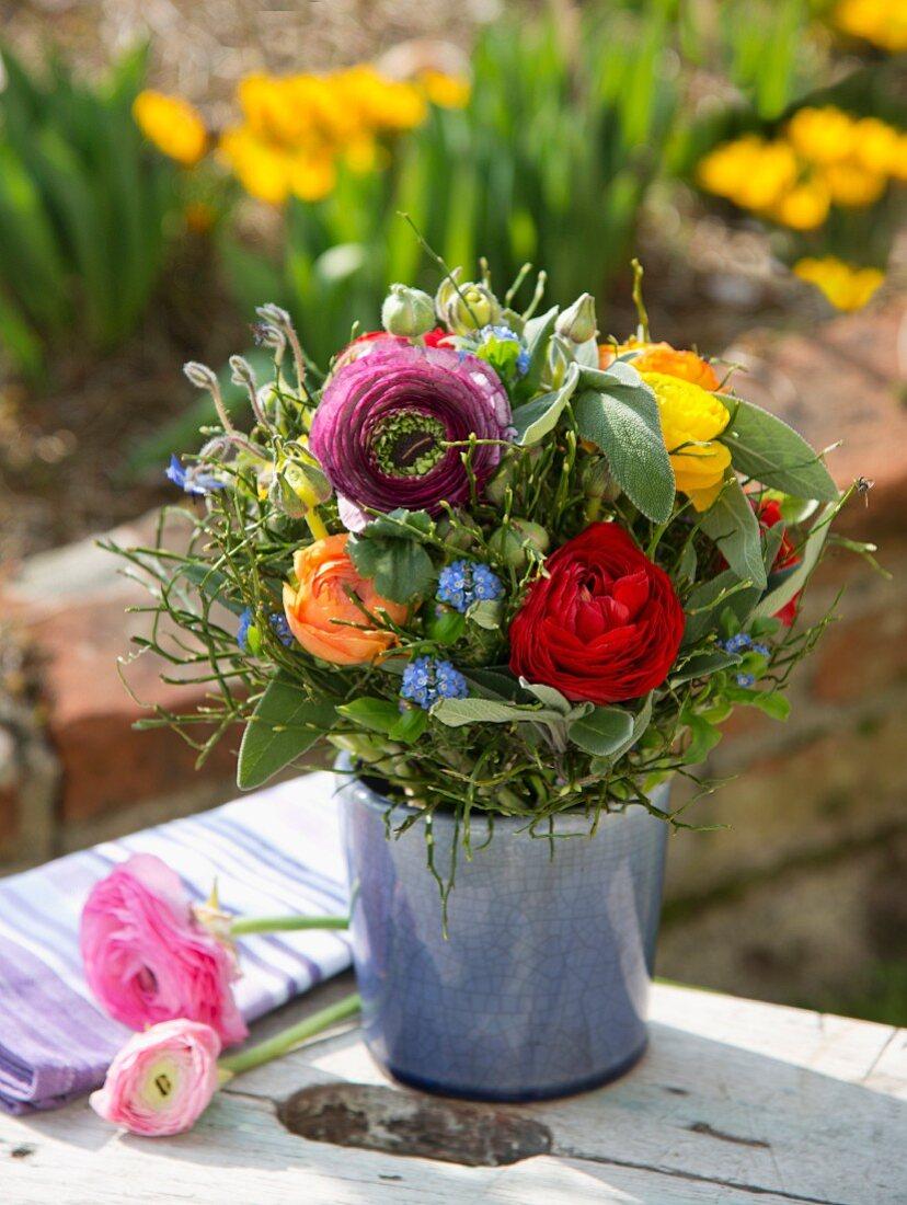 Colourful summer posy of ranunculus in ceramic pot