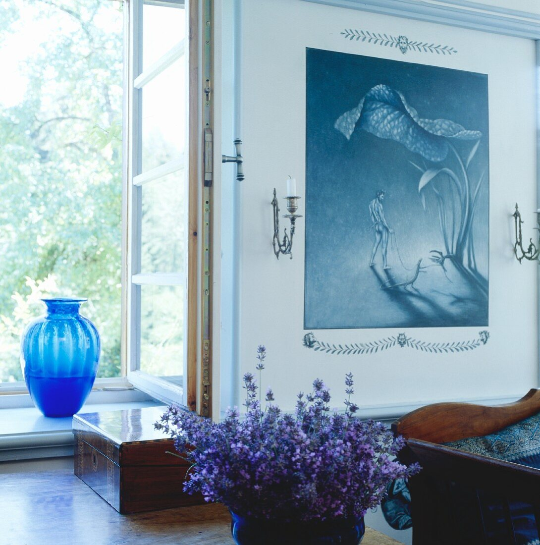 Bowl of purple flowers on table in front of window with blue glass vase on windowsill; painting in shades of blue to one side