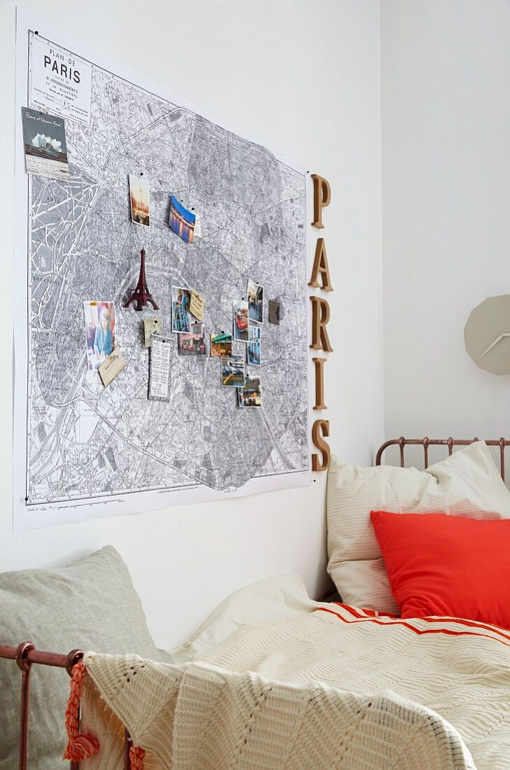 And map of Paris decorated with souvenirs hung above a bed