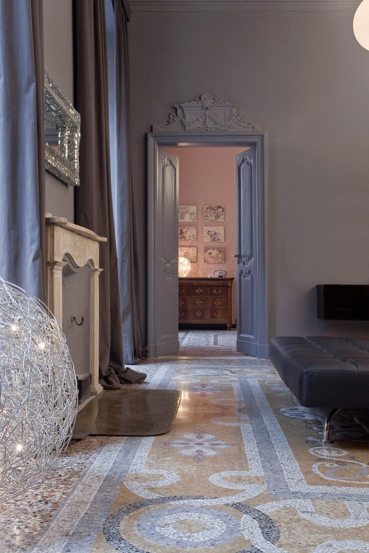 Blick durch Kassetten-Tür mit Stuckelement auf antike Kommode, Terrazzoboden